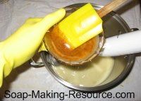mixing annatto seed powder into soap